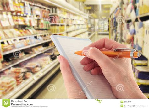Hand With Pen Writing Shopping List In Supermarket Stock